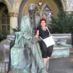 fekete ruhás nő, fehér szatyorral, a szobor árnyékában pózol